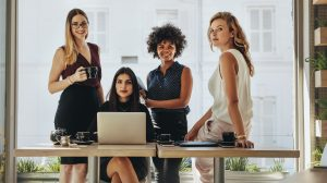 Portrait of four successful young businesswomen together in office. Group of multi-ethnic businesswomen looking at camera.