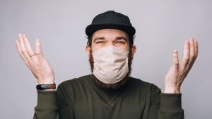 Photo of confused young bearded hipster man gesturing and wearing anti covid mask