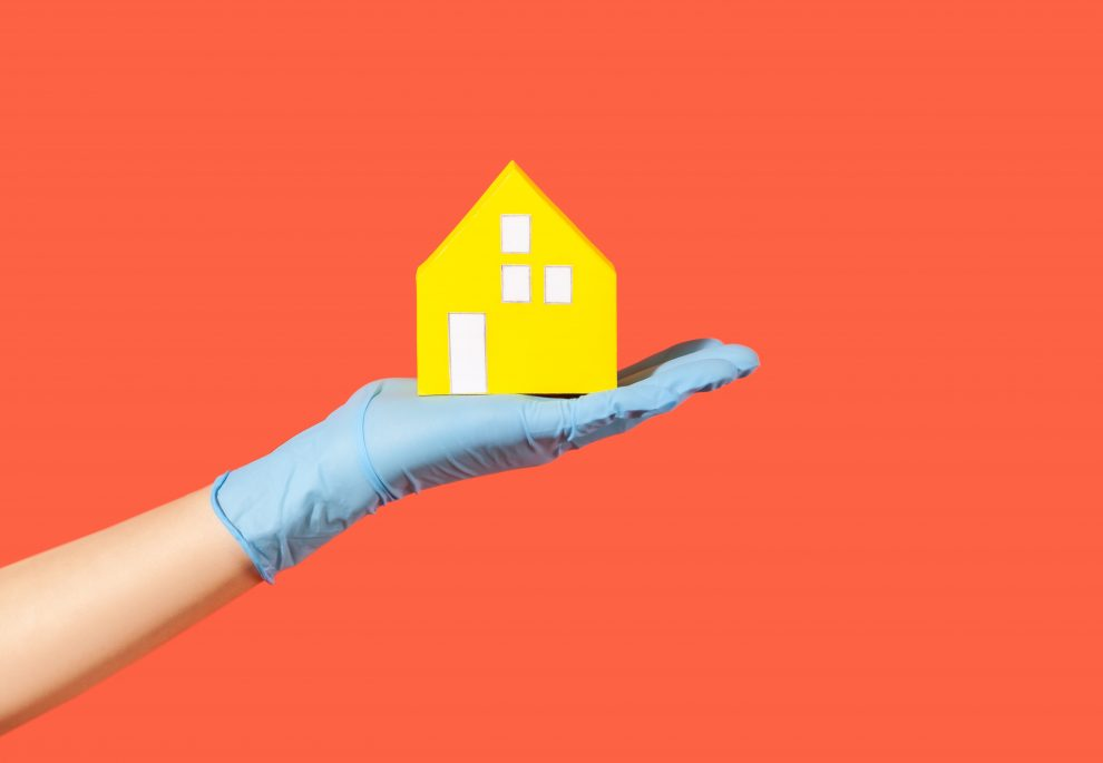 Closeup hand in surgical gloves holding paper house, message to stay safe at home on quarantine while contagious disease 2019-ncov spread, coronavirus outbreak. studio shot isolated on red background