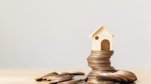 Property investment and home mortgage financial concept. Money coin stack with wooden house