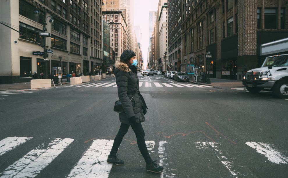 Woman wearing surgical mask going through crosswalk in midtown manhattan.Concept of Coronavirus, COVID-19 and quarantine