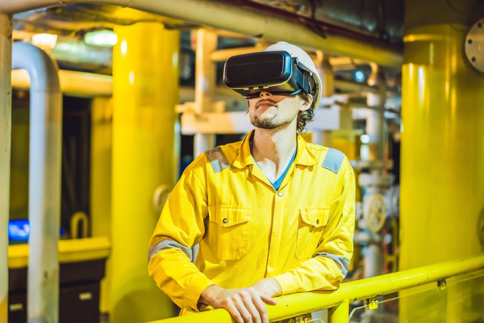 Young woman in a yellow work uniform, glasses and helmet uses virtual reality glasses in industrial environment,oil Platform or liquefied gas plant.