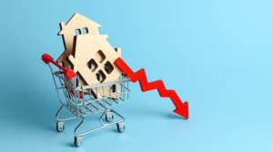 Arrow to down and houses in shopping cart on blue background. Market growth in real estate prices.