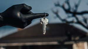 Keys in hand in black glove. Use alcohol spray to corona virus and kill germs at the key of the house or office regularly. Covid-19 ncov or coronavirus quarantine concept.